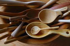 Plusieurs remettent les cuillères en bois découpées disposées dans une cuvette en bois Photo libre de droits