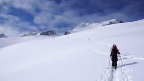 Plusieurs skieurs backcountry augmenter et s'élever à une crête à distance de moutain en Suisse un beau jour d'hiver images libres de droits
