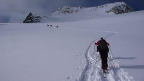 Plusieurs skieurs backcountry augmenter et s'élever à une crête à distance de moutain en Suisse un beau jour d'hiver photographie stock libre de droits