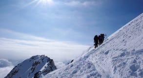 Plusieurs skieurs backcountry augmenter et s'élever à une crête à distance de moutain en Suisse un beau jour d'hiver photo stock