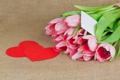 Plusieurs tulipes roses avec peu de carte postale et deux coeurs rouges Images stock