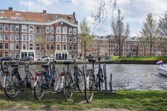 Plusieurs vélos sur le stationnement près du canal grand à Amsterdam avec les bâtiments bruns comme fond Photos stock