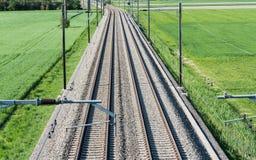 Plusieurs voies ferrées menant à l'horizon au milieu des champs verts Photographie stock