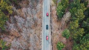 Plusieurs voitures avec des kayaks sur la galerie conduisant sur la route parmi des arbres banque de vidéos