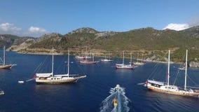 Plusieurs yachts avec le groupe de personnes non identifié faisant des watersports d'équitation de bateau de banane dans la côte  clips vidéos