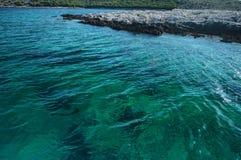 Pluskocząca powierzchnia woda morska i szczegół skalista wysepka kryształu - jasna, przejrzysta, Zdjęcia Royalty Free