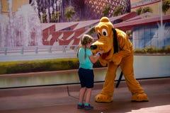 Plut?o que joga com a menina em Epcot em Walt Disney World 2 fotografia de stock royalty free