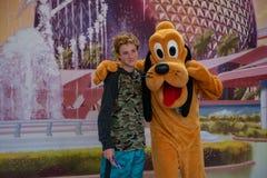 Pluto που αγκαλιάζει το μικρό παιδί σε Epcot στον κόσμο Walt Disney στοκ φωτογραφία με δικαίωμα ελεύθερης χρήσης