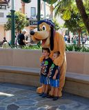 Pluto at California Adventure. Goofy getting his picture taken with two little boys or tourist at California Adventure near Disneyland in Anaheim California, USA Royalty Free Stock Photo