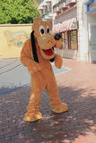 Pluto at Disneyland. Anaheim, California, USA - May 30, 2014: Pluto, a Disney cartoon character, is greeting tourists at Main Street U.S.A. in Disneyland Park Stock Photos