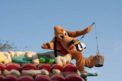 Pluto the Pup on float in Disneyland Parade. Pluto the Pup is riding on a float in Disneyland's A Christmas Fantasy Parade. Very popular Christmastime parade at stock photos
