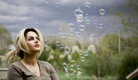 Plyaing with bubbles. Girl watching bubble maker makings bubbles Royalty Free Stock Photos