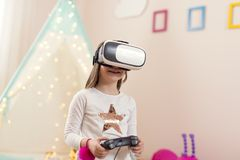 Plying VR video games. Little girl wearing virtual reality headset, playing video games in a playoom and having fun stock image