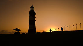 Plymouth lighthouse at sunset. Plymouth lighthouse silhouetted at sunset in Devon, England Royalty Free Stock Images