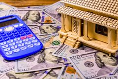 Plywood model of the house, calculator and one hundred dollar banknotes. Loan, real estate concept. Plywood model of house, calculator and one hundred dollar royalty free stock photo