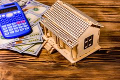 Plywood model of the house, calculator and one hundred dollar banknotes. Loan, real estate concept. Plywood model of house, calculator and one hundred dollar royalty free stock photos