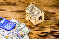 Plywood model of the house, calculator and one hundred dollar banknotes. Loan, real estate concept. Plywood model of house, calculator and one hundred dollar stock photos