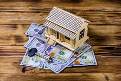 Plywood model of the house, key and one hundred dollar banknotes. Loan, real estate concept. Plywood model of house, key and one hundred dollar banknotes. Loan stock images