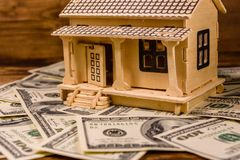 Plywood model of the house and one hundred dollar banknotes. Loan, real estate concept. Plywood model of house and one hundred dollar banknotes. Loan, real stock photo