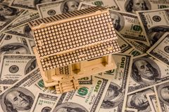 Plywood model of the house and one hundred dollar banknotes. Loan, real estate concept. Plywood model of house and one hundred dollar banknotes. Loan, real stock image