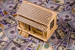 Plywood model of the house and one hundred dollar banknotes. Loan, real estate concept. Plywood model of house and one hundred dollar banknotes. Loan, real royalty free stock photography