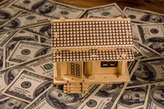Plywood model of the house and one hundred dollar banknotes. Loan, real estate concept. Plywood model of house and one hundred dollar banknotes. Loan, real royalty free stock photo