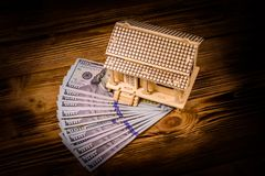 Plywood model of the house and one hundred dollar banknotes. Loan, real estate concept. Plywood model of house and one hundred dollar banknotes. Loan, real stock photography