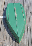 Plywood skiff on a wood deck. The hull of a green painted plywood skiff upside down on a deck Stock Photography