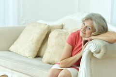 Pmature woman sitting in vintage sofa Stock Images