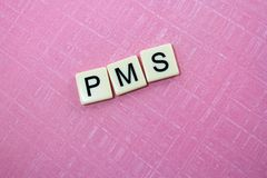 PMS. The acronym for premenstrual syndrome spelled out in tiles against a pink background Royalty Free Stock Image