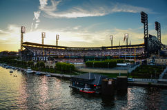 PNC Park - Pittsburgh, PA. Lights on at twilight at Pittsburgh Pirates PNC Park arena with stadium seats filled by spectators watching a baseball game Royalty Free Stock Photo