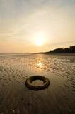 Pneu abandonné sur la plage quand le soleil se couche Photographie stock libre de droits