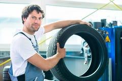 Pneu changeant de mécanicien automobile dans l'atelier images stock