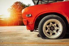 Pneu crevé de roue de voiture dans le stationnement images stock