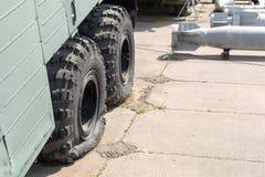 Pneu crevé de vieux camion lourd militaire Bombes polyvalentes d'air sur le fond Délabrement d'armée et concept de dégradation images libres de droits