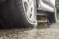Pneu crevé de voiture dans le jour pluvieux photo stock
