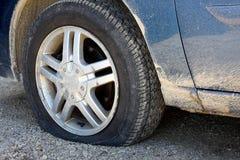Pneu crevé sur la vieille voiture sale photographie stock libre de droits