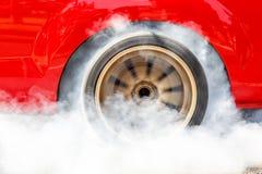 Pneu d'arrière de burn-out de voiture de voiture à moteur gonflé avec de la fumée photographie stock libre de droits