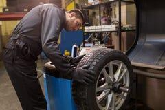 Pneu de voiture de équilibrage de mécanicien automobile à l'atelier photographie stock