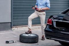 pneu de voiture changeant d'homme Photographie stock