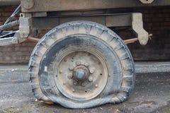 Pneu liso sujo danificado do carro do vintage no parque velho da estrada fotos de stock royalty free