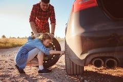 Pneu quebrado em mudança do pai e da filha durante a viagem por estrada rural do verão foto de stock royalty free