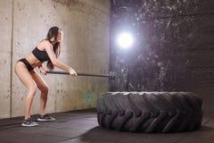 Pneu sensationnel de femme grand avec le marteau de forgeron pendant la séance d'entraînement intense dans le gymnase d'ajustemen images libres de droits