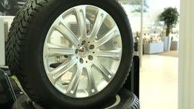 Pneumático novo do carro com disco Vendendo uma roda nova do automóvel Vista do carro novo da fileira na sala de exposições nova  vídeos de arquivo