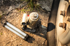Pneumatic car jack next to old tire Royalty Free Stock Photos