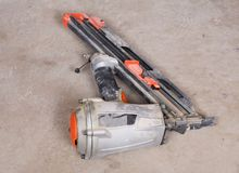 Pneumatic collated framing nailer in the basement. Of house under remodeling royalty free stock image
