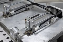 Pneumatic cylinder setup on machine. In manufacturing stock photo
