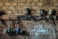 Pneumatic spray guns and protective respiratory masks hanging on the wall. Of the carpenter painting room royalty free stock photo