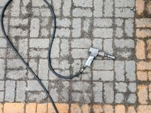 Pneumatic wrench with a long hose lying on the floor of stone tiles. Top view royalty free stock image