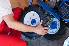 Pneumatico del montaggio dell'uomo su un attrezzo del motore della benzina Immagine Stock Libera da Diritti